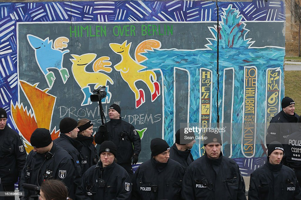 Police guard a section of the East Side Gallery, which is the longest still-standing portion of the former Berlin Wall, before construction workers attempted to remove it with a crane on March 1, 2013 in Berlin, Germany. A real estate developer is planning to build a 14-storey apartment building between the Wall and the Spree River and needs to remove a 25-meter long Wall section in order to allow access to the construction site. Critics, including East Side Gallery mural artists and Spree River embankment development opponents, decry the move, citing the importance of the East Side Gallery's status as a protected landmark and a major tourist attraction. The East Side Gallery is approximately 1.3 kilometers long.