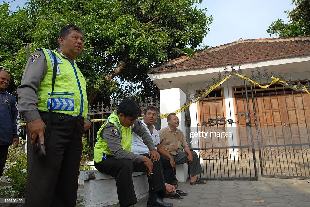 CORRECTION - BYLINE Police guard outside a house, used as a boarding school, in Nganjuk, East Java, on November 13, 2012. Indonesian police detained 48 students and a teacher from an Islamic boarding school and seized firearms and sharp weapons, a spokesman said November 13, in the nation's latest terror raid.