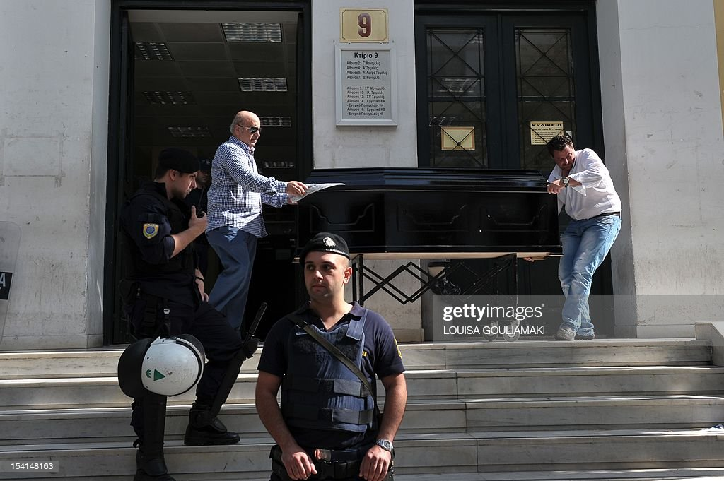 Police guard outside the Athens court building while workers remove a coffin with the body of a man killed during a trial on October 15, 2012.A Greek Roma woman killed a man accused of murdering her son Monday when she opened fire inside an Athens court, also wounding another man, officials said.