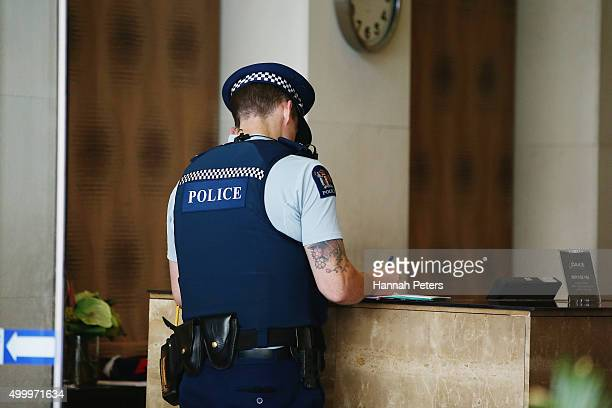Police guard the entrance to the Auckland Harbour Oaks Apartments on December 5 2015 in Auckland New Zealand Police are hunting for a shooter after a...