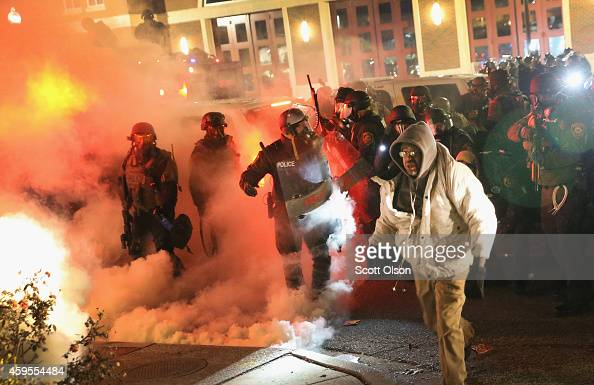 Police guard the Ferguson police department as rioting erupts following the grand jury announcement in the Michael Brown case on November 24 2014 in...