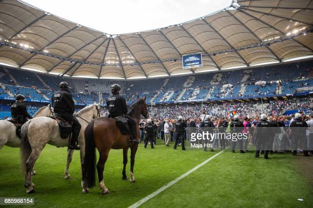 Police guards as fans of Hamburg celebrate in the pitch after the Bundesliga match between Hamburger SV and VfL Wolfsburg at Volksparkstadion on May...