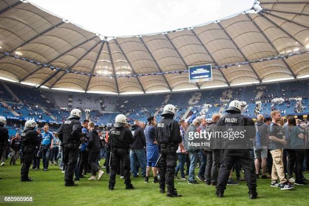 Police guards as fans of Hamburg celebrate in the pitch as after the Bundesliga match between Hamburger SV and VfL Wolfsburg at Volksparkstadion on...