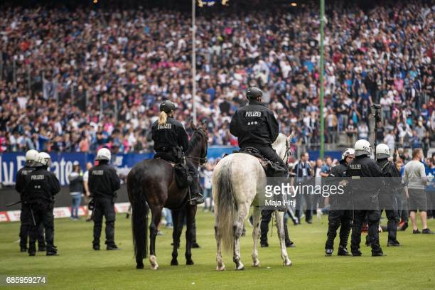 Police guards as fans of Hamburg storm the pitch after the Bundesliga match between Hamburger SV and VfL Wolfsburg at Volksparkstadion on May 20 2017...