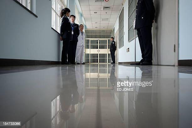 Police guards stand in a hallway of a hospital inside the No1 Detention Center during a government guided tour in Beijing on October 25 2012 The rare...