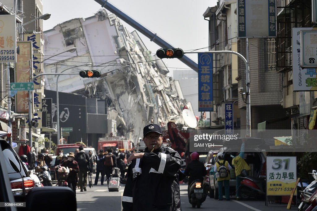 A police guides traffic past the collapsed Wei Kuan complex building on the second day of rescue operations following a 6.4 magnitude earthquake in southern Taiwan's city of Tainan on February 7, 2016. Rescuers raced against time February 7 to free more than 100 people buried beneath the rubble of apartment blocks felled by an earthquake in southern Taiwan that left 19 dead, as an investigation was launched into the building collapse. AFP PHOTO / Sam Yeh / AFP / SAM YEH