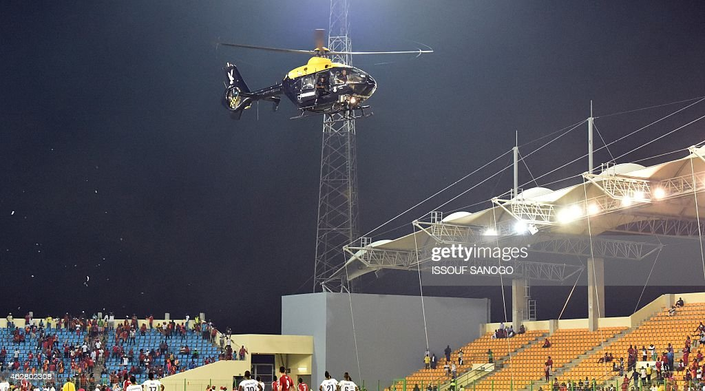 A police helicopter flies over the statdium during an interruption of the 2015 African Cup of Nations semifinal football match between Equatorial...
