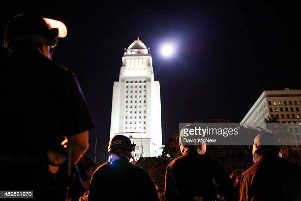 A police helicopter flies past City Hall as police and protesters face off in front of LAPD Headquarters following the grand jury decision not to...