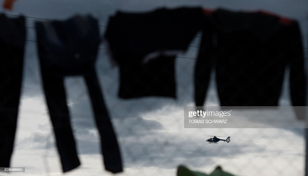 A police helicopter patrols over a makeshift camp for migrants and refugees near the village of Idomeni not far from the Greek-Macedonian border on May 4, 2016. Some 54,000 people, many of them fleeing the war in Syria, have been stranded on Greek territory since the closure of the migrant route through the Balkans in February. / AFP / TOBIAS