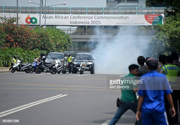 TOPSHOT Police hide behind vehicles during an exchange of gunfire with suspects hiding near a Starbucks cafe when another blast happens in Jakarta on...
