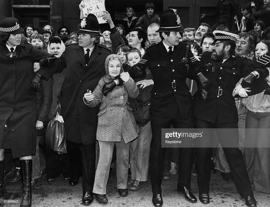 Police hold back crowds outside Dewsbury court, Yorkshire as Peter Sutcliffe appears in court after his arrest in connnection with the 'Yorkshire Ripper' murders, January 1981.