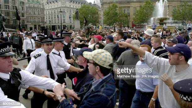 Police hold back demonstrators at a rally for the Muslim group AlMuhajiroun in London's Trafalgar Square
