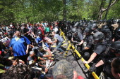 Police hold back fast food workers and activists demonstrating at the McDonald's corporate campus on May 21 2014 in Oak Brook Illinois The...