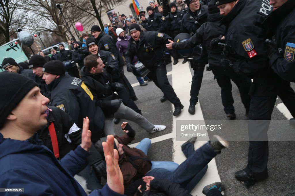 Police hold back people as they demonstrate during a protest against the Munich Security Conference in the city centre on February 2, 2013 in Munich, Germany. The Munich Security Conference brings together senior figures from around the world to engage in an intensive debate on current and future security challenges and remains the most important independent forum for the exchange of views by international security policy decision-makers.