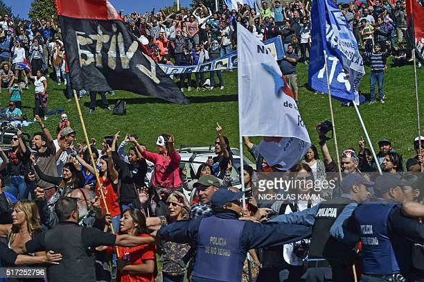 Police hold back protestors as the motorcade of US President Barack Obama drives by in Bariloche Argentina on March 24 2016 President Barack Obama...