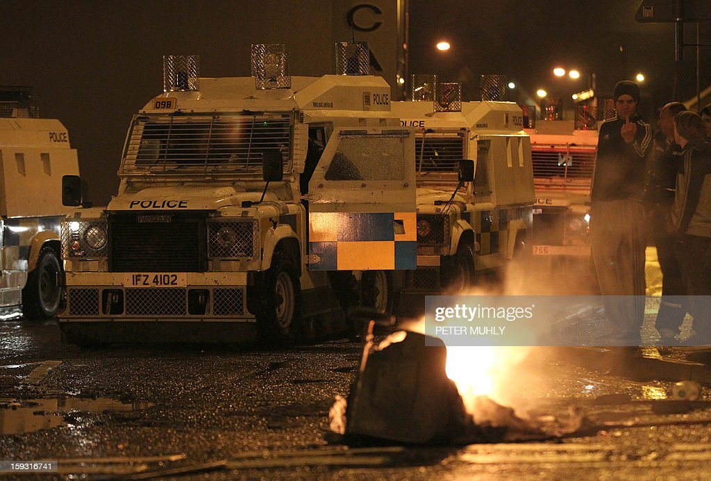 Police in armoured vehicles secure the area near burning debris ain Carrickfergus, near Belfast in County Antrim, Northern Ireland on January 11, 2013 after a Loyalist demostration as part of an ongoing campaign opposing Belfast City Council's decision to restrict the days on which the British Union Flag will fly over the City Hall. Pro-British demonstrators have taken to the streets, in sometimes violent protest, almost every night since December 3, when the city council announced it would no longer fly the Union Flag all year round at City Hall. Protesters have pelted police with petrol bombs, fireworks, bottles and stones.