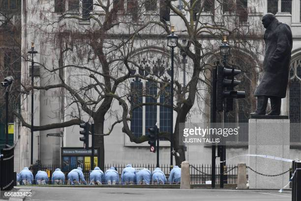 TOPSHOT Police in forensic suits search Parliament Square outside the Houses of Parliament in central London on March 23 2017 the day after the March...