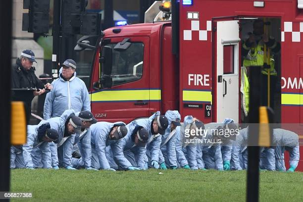TOPSHOT Police in forensic suits search the a grassed area in Parliament Square outside the Houses of Parliament in central London on March 23 2017...