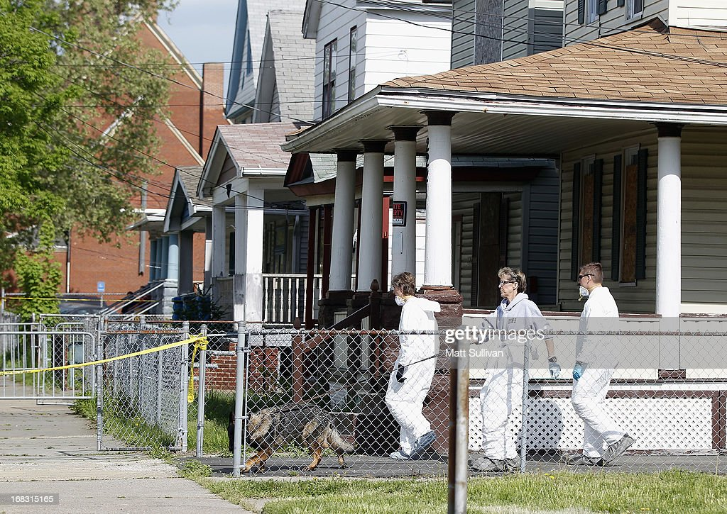 Police in protective suits investigate houses down the street from the house where three women were held captive for close to a decade May 8, 2013 in Cleveland, Ohio. Amanda Berry, Gina DeJesus, and Michelle Knight managed to escape their captors on May 6, 2013. Ariel Castro was charged with kidnap and rape. His brother Pedro and Onil Castro, were taken into custody but not charged.
