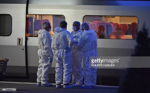 Police in protective suits stand on a platform next to a Thalys train of French national railway operator SNCF at the main train station in Arras...