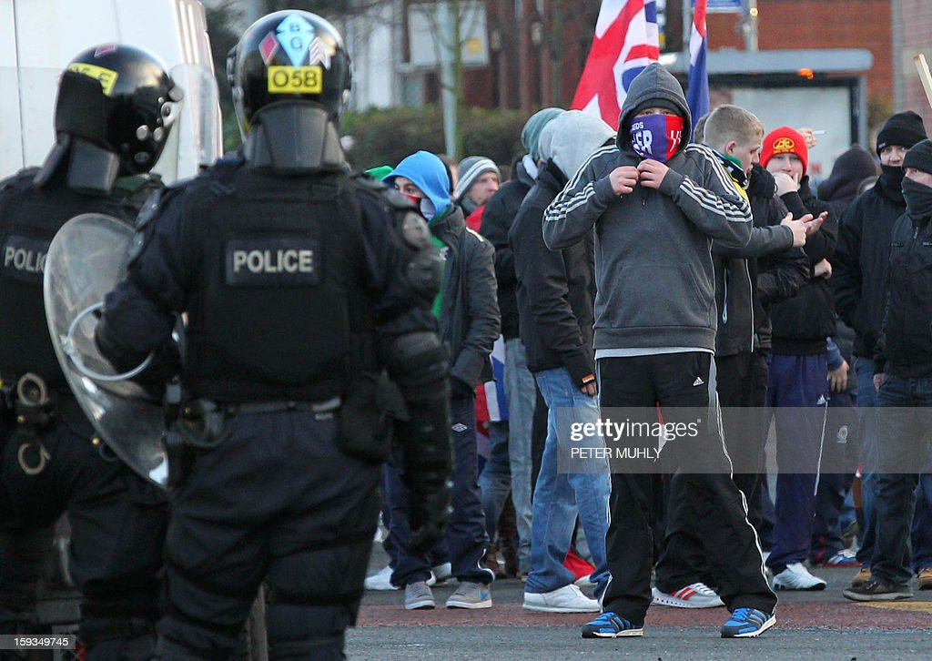 Police in riot gear and armoured vehicles clash with Union Flag waving loyalist protesters in east Belfast, Northern Ireland on January 12, 2013 after the latest loyalist march against the decision to limit the days on which the Union Flag would be flown over Belfast City Hall. Northern Irish demonstrators loyal to Britain clashed with nationalists and police on Saturday in fresh protests against curbs on flying the British flag, leaving four officers injured, police said. The clashes were the latest to blight the British province after more than five weeks of violent disorder over the flag issue. AFP PHOTO / PETER MUHLY
