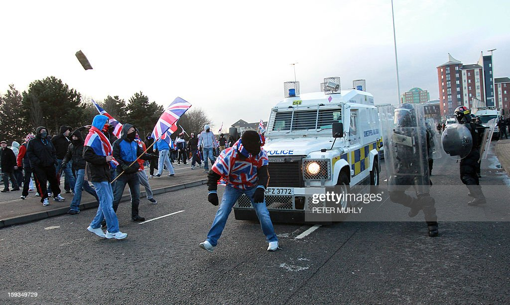 Police in riot gear and armoured vehicles clash with Union Flag waving loyalist protesters, during violence between, loyalists, nationalists and police in east Belfast, Northern Ireland on January 12, 2013 after the latest loyalist march sparked by the decision to limit the days on which the Union Flag would be flown over Belfast City Hall. Northern Irish demonstrators loyal to Britain clashed with nationalists and police on Saturday in fresh protests against curbs on flying the British flag, leaving four officers injured, police said. The clashes were the latest to blight the British province after more than five weeks of violent disorder over the flag issue. AFP PHOTO / PETER MUHLY