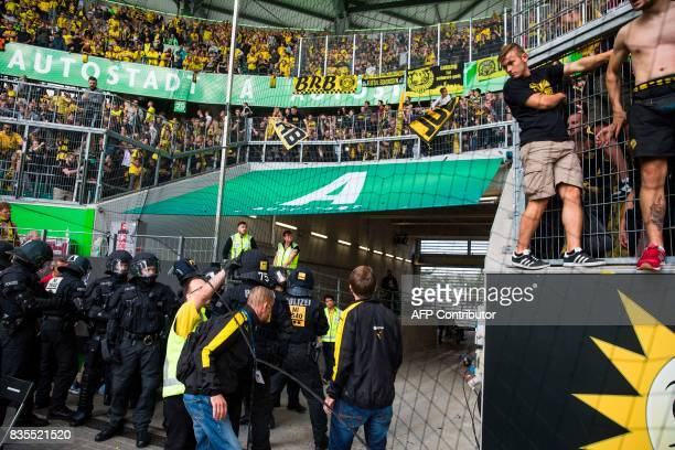 Police in riot gear arrests a man who ripped off a Dortmund banner as Dortmund fans are told to stay back by a steward after the German First...