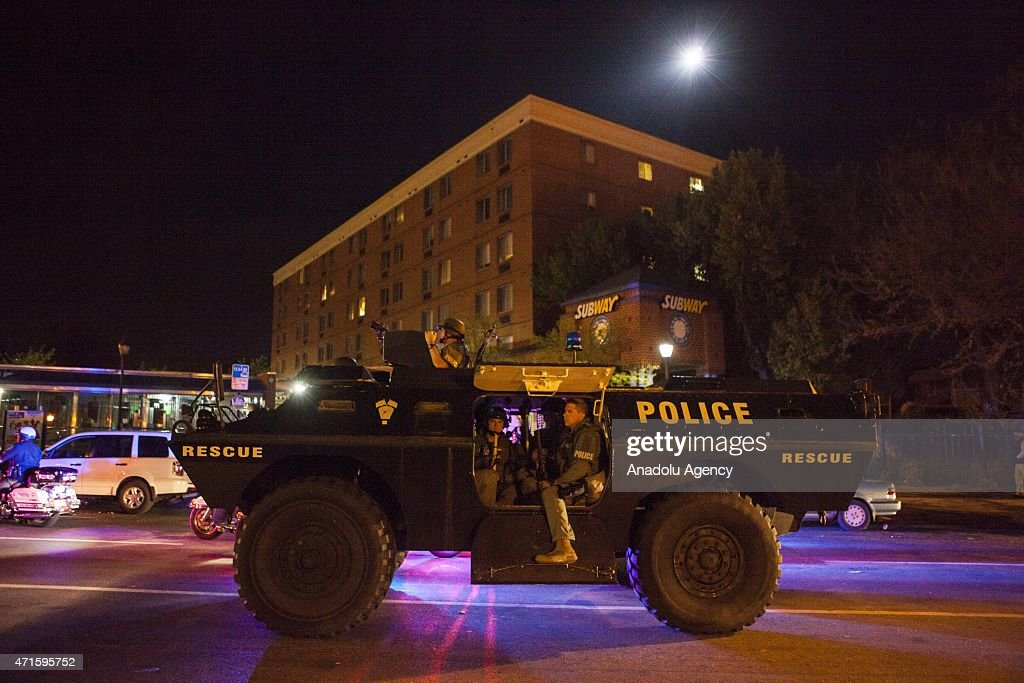 Police in riot gear arrive in a armored vehicle at the intersection of West North Avenue and Pennsylvania Avenue to enforce the declared curfew in...