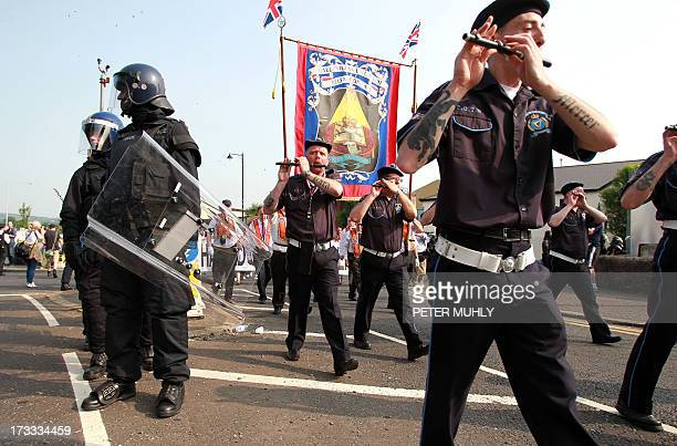 Police in riot gear escort line the streets as protestant Orangemen march through the Catholic Ardoyne district of north Belfast Northern Ireland on...