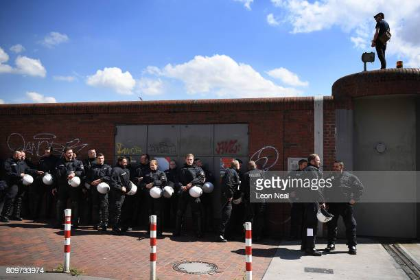 Police in riot gear prepare in the shade before a 'Welcome to Hell' protest march ahead of the G20 Summit in the harbour area of Hamburg on July 6...