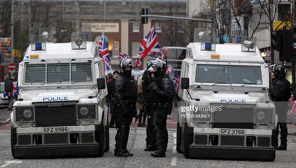 Police in riot gear stand guard as loyalist demonstrators march outside Belfast City Hall in protest over Belfast city council's decision to restrict the number of days the British Union Flag can be flown over the city hall in Belfast, Northern Ireland on January 5, 2013. Nine officers were injured and 18 people arrested in fresh violence overnight on the streets of Belfast, police said. Tensions have risen in the British province since councillors voted on December 3, 2012 to limit the number of days the Union flag can fly over the City Hall to 17, outraging loyalists who believe Northern Ireland should retain strong links to Britain. AFP PHOTO / PETER MUHLY