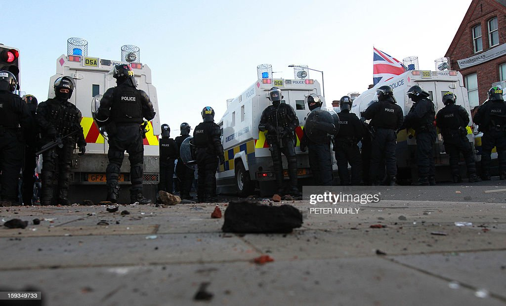 Police in riot gear stand with their armoured vehicles with bits of brick and rock thrown at police littering the floor during violence between, loyalists, nationalists and police in east Belfast, Northern Ireland on January 12, 2013 after the latest loyalist march against the decision to limit the days on which the Union Flag would be flown over Belfast City Hall. Northern Irish demonstrators loyal to Britain clashed with nationalists and police on Saturday in fresh protests against curbs on flying the British flag, leaving four officers injured, police said. The clashes were the latest to blight the British province after more than five weeks of violent disorder over the flag issue. AFP PHOTO / PETER MUHLY