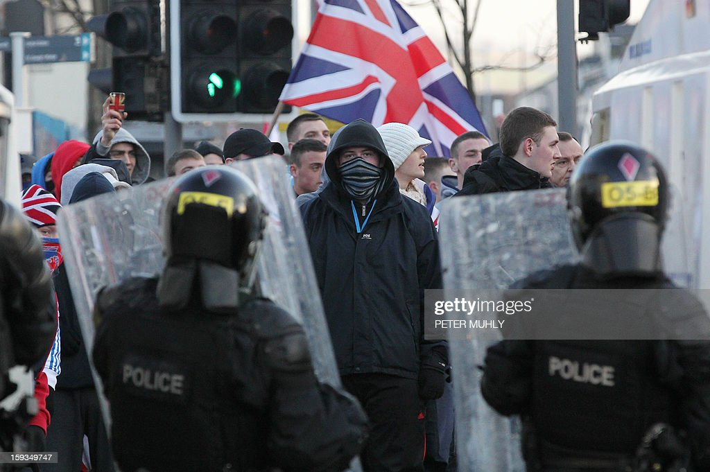 Police in riot gear try to contain with Union Flag waving loyalist protesters during clashes in east Belfast, Northern Ireland on January 12, 2013 after the latest loyalist march against the decision to limit the days on which the Union Flag would be flown over Belfast City Hall. Northern Irish demonstrators loyal to Britain clashed with nationalists and police on Saturday in fresh protests against curbs on flying the British flag, leaving four officers injured, police said. The clashes were the latest to blight the British province after more than five weeks of violent disorder over the flag issue. AFP PHOTO / PETER MUHLY