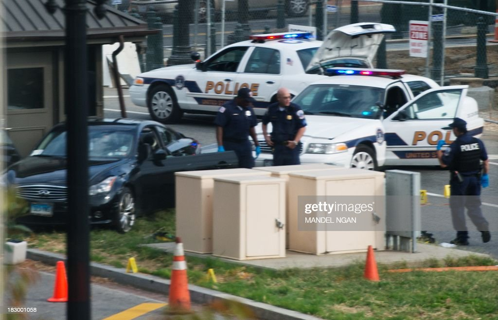 Police inspect a car on the median of Constitution Ave in front of the Hart Senate Office Building following reports of a shooting on October 3, 2013 in Washington, DC. A car described as black in color is suspected in the shooting incident on Capitol Hill. AFP PHOTO/Mandel NGAN