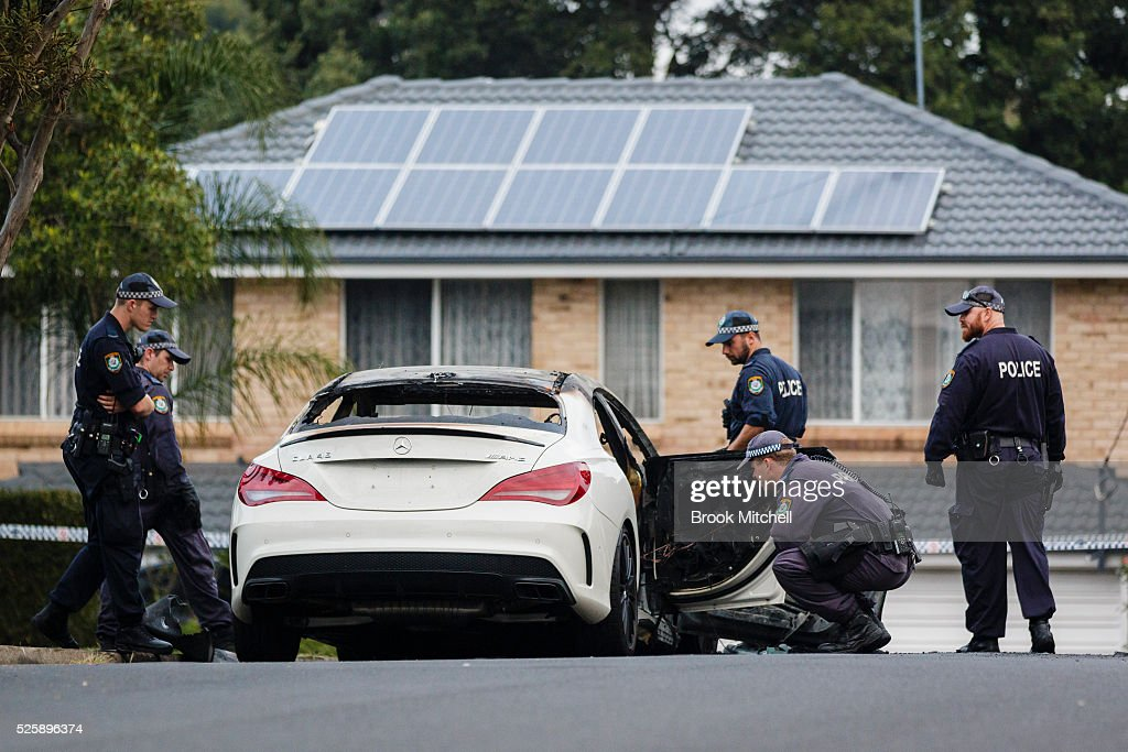 Police inspect the burnt-out remains of a vehicle used during a shooting at Bankstown Central Shopping Centre on April 29, 2016 in Sydney, Australia. One man has been confirmed dead, with two others injured.
