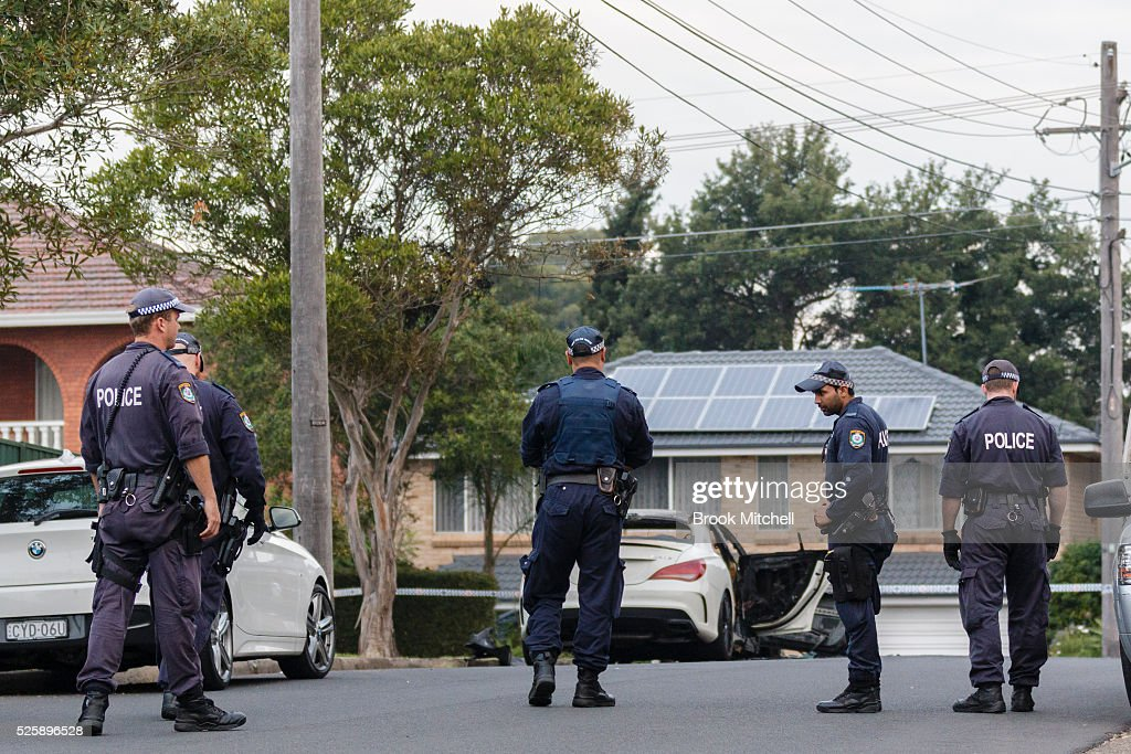 Police inspect the burnt-out remains of a vehicle used during a shooting at Bankstown Central Shopping Centre on April 29, 2016 in Sydney, Australia. The car was found at Salamnder PL, Greenacre. One man has been confirmed dead, with two others injured.