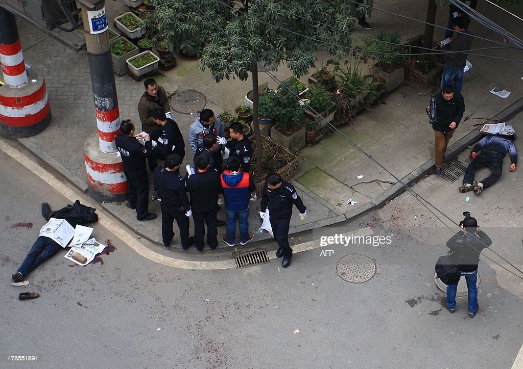 Police inspect the crime scene where attackers armed with knives killed three people in Changsha, central China's Hunan province on March 14, 2014. Attackers armed with knives killed three people in China on March 14, an official said, ruling out terrorism two weeks after a mass stabbing blamed on Xinjiang militants left 29 people dead and stunned the nation. CHINA OUT AFP PHOTO