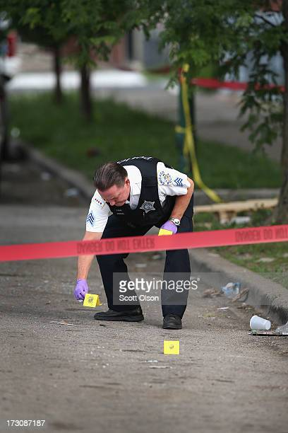 Police investigate a crime scene where seven people were shot on July 6 2013 in Chicago Illinois Two days earlier and half of a block away Steve...