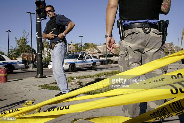 Police investigate a murder in which a teenager going home from school was shot while waiting for the bus September 16 2003 on the west side of...