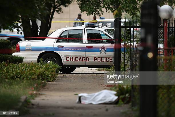 Police investigate the shooting death of 14yearold Tommy McNeal whose body is covered by a sheet on the sidewalk on September 20 2013 in Chicago...