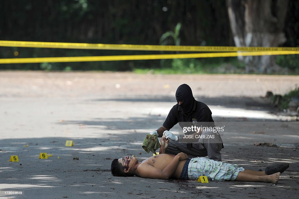 A police investigator collects evidence beside a murdered man in the town of Quezalteque, 25 km west of San Salvador, on July 5, 2013. The victim, 19-year-old Carlos Ernesto Alvarez, a tuk-tuk driver, was killed allegedly by gang members when he was cleaning his vehicle. According to the forensic departament 66 people were murdered in El Salvador in a raise in violent deaths in the first four days of July. Murders had dropped after a gang truce was reached in March 2012. AFP PHOTO/Jose CABEZAS
