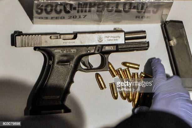 A police investigator examines a firearm recovered from the scene where an offduty police officer was shot dead by motorcycle riding assailants in...