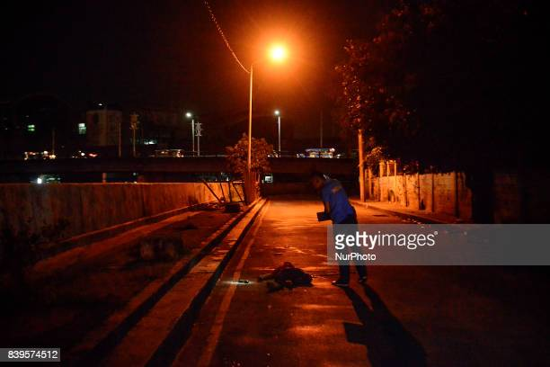 A police investigator inspects the body of a man who was killed by police during a police operation in Manila Philippines August 17 2017 Amidst the...