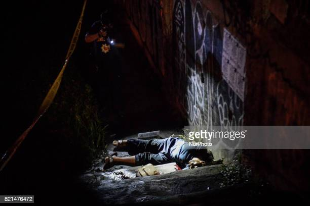 A police investigator inspects the body of Antonio Vinculado after he was killed by police in what they say was a shootout with police in Paranaque...