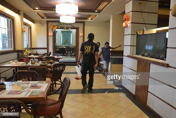 A police investigator inspects the crime scene where Chinese consul general Song Ronghua was wounded after a shooting incident at a restaurant in...