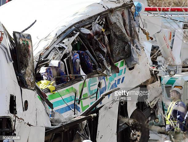 A police investigator looks at a crashed bus in Karuizawa in Nagano prefecture central Japan on January 15 after it ran off a mountain road Fourteen...