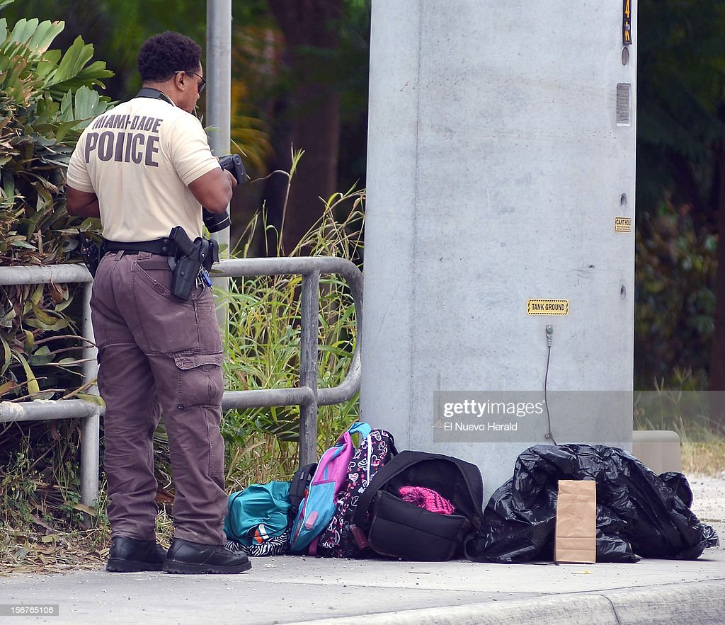 Police investigator photographs the school backpacks taken off a school bus after a student shot and killed a 13-year-old girl in front of her younger sister and seven other children on a school bus Tuesday morning, November 20, 2012, in Homestead, Florida.
