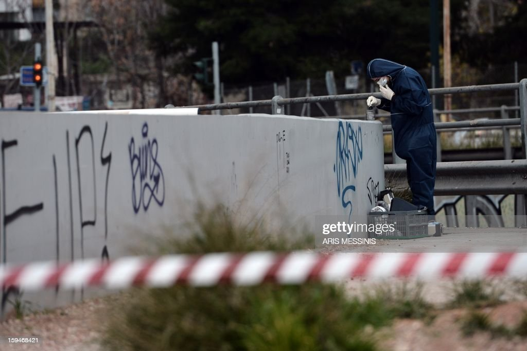 A police investigator searches for evidences on January 14, 2013 outside the headquarters of New Democracy conservative party in Athens. Shots were fired early on January 14 near the offices of main Greek ruling party New Democracy in Athens, police said, after a recent wave of arson attacks against political offices.
