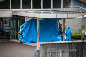 Police investigator try to cover the main entrance of Tsukui Yamayurien the building of the crime scene Police arrested 26yearold Satoshi Uematsu...