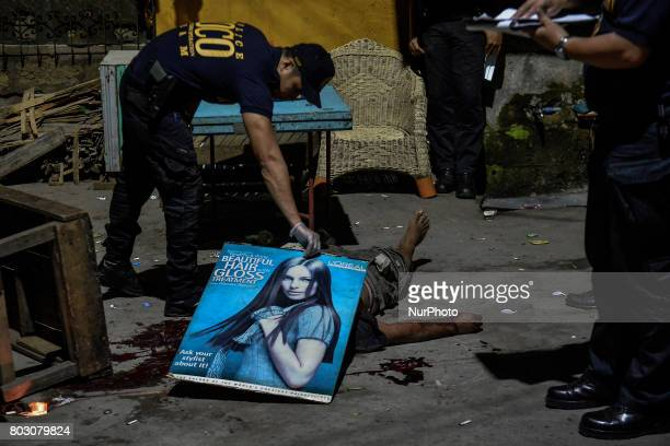 A police investigator uses a cardboard poster to cover the body of a shooting victim in Quezon city north of Manila Philippines February 9 2017...